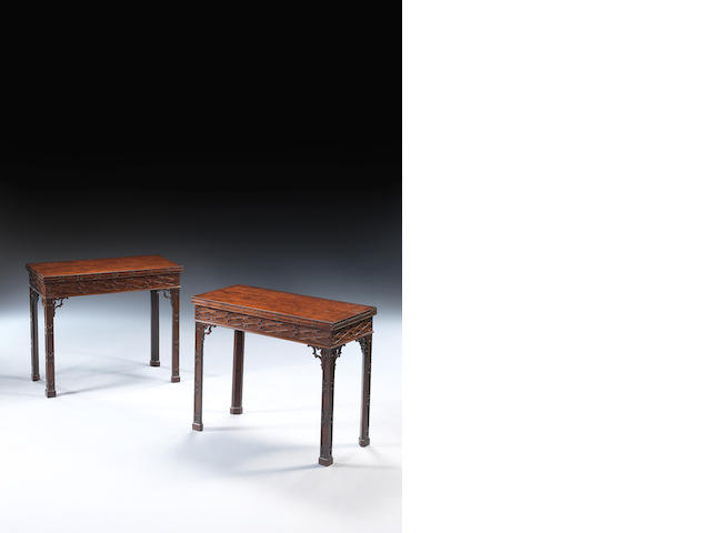 A pair of George III mahogany blind fret carved card tables, formerly with concertina actions in the Chippendale Gothick taste