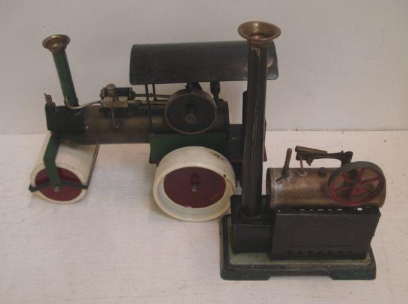 A painted metal steam driven model traction engine, a small model steam engine, a model boiler, three model driving wheels, burners and funnels, a hot air boat and one other