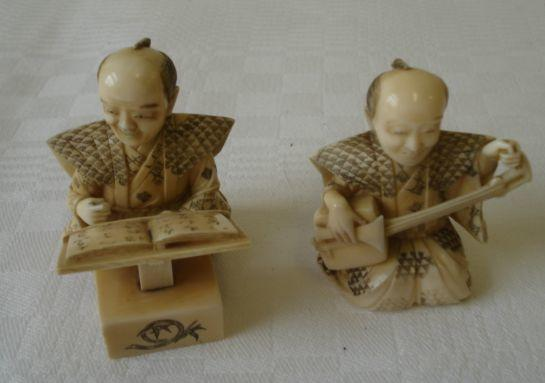 A pair of Japanese carved and stained ivory okimono, Meiji circa 1900, one as an instrument player kneeling in traditional dress, the other similarly dressed reading from a book, 6.5cm, one with signed inlaid mother of pearl panel.