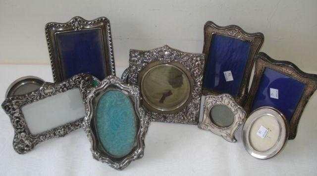 A good collection of silver faced easel photograph frames,  including, a landscape frame with pierced scrolls and cherubs, by William Comyns, 1903, image size 7.5 x 11.5cm, an Art Nouveau frame decorated with irises, circular centre 5cm diameter, Birmingham 1902, another double framed with scrolling flowers, 1903, a Rococo fronted frame on velvet, Sheffield 1900 and seven others. (11)