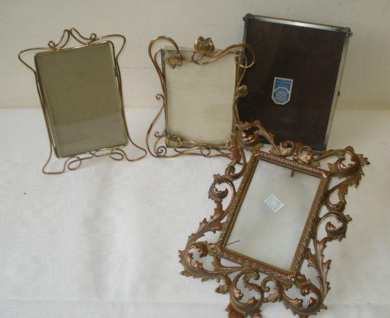 A polished brass Art Nouveau style photograph frame, the scrolling frame with flowerheads, another twisted brass frame, a gilt iron frame and one other.(4)