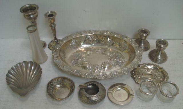 A late Victorian oval silver fruit dish, Hilliard & Thompson, Birmingham 1899, foliate pierced and embossed, 27.5cm, and the following silver, a scallop shell butter dish, bon bon dish, late Victorian foliate embossed ashtray, Birmingham 1891, another ashtray, pair of dwarf candlesticks, another, a spill vase, 12ozs, weighable, also a pair of mounted cut glass salt cellars and a spill vase and a foreign metalware ashtray.