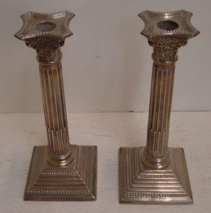 A pair of George III style silver Corinthian column candlesticks, makers mark HYC, Birmingham 1964, with beaded borders, detachable nozzles, on stepped square bases, 24.5cm.