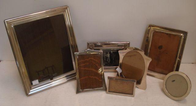 A collection of six George V and later silver mounted easel photograph frames, including two of shaped outline, Birmingham 1910 & 1920, one with oval apperture, another Birmingham 1917, sight size 17.5 x 10.5cm, a smaller similar and a circular example, a large modern rectangular photograph frame, with moulded edge, sight size 20 x 24.5cm and one other. (7)