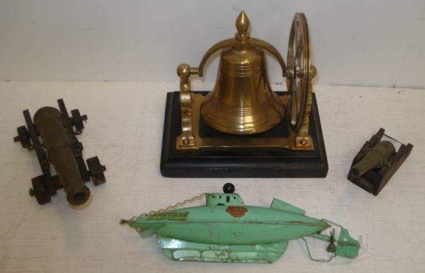 A Sutcliffe model Nautilus tinplate submarine, copyright Walt Disney Productions, 24cm, two miniature brass canons on wooden carriages and a brass bell on ebonised base. (4)