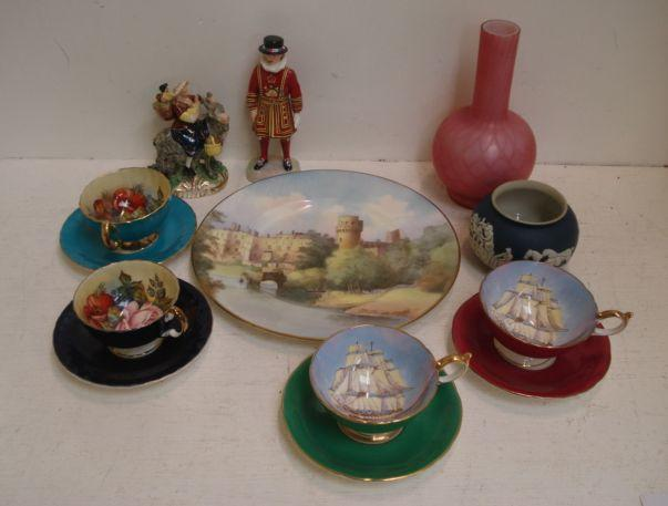 A Minton plate, decorated with a view of Warwick Castle by C Peake, 27.5cm, two Aynsley tea cups and saucers painted with roses by J A Bailey, two others, painted with fully rigged clippers, by D Jones, Adams blue jasper dip bowl, quilted pink satin glass bottle vase, Adderley figure of a Beefeater and other items.