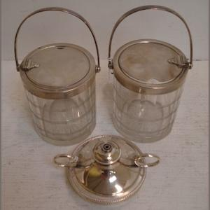 A pair of George V silver mounted cylindrical cut glass preserves jars, Hukin & Heath, Birmingham 1925, the swing handles activating the hinged covers, 15cm, and a two handled circular cigar lamp, Elkington & Co, Birmingham 1925 with egg and tongue border fitting inside four matching ashtrays, 6ozs weighable. (2)
