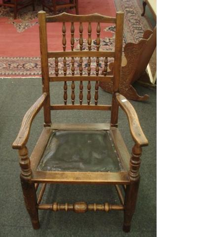 An ash and elm Lancashire spindle back elbow chair, late 18th/early 19th Century, with later upholstered seat, on rounded tapering legs.