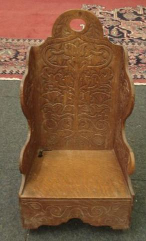 A child's oak wing back rocking chair, 19th Century, carved with stylised flowering and fruiting branches, solid seat.