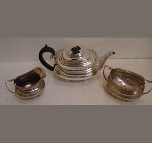 A George III style silver three piece tea service, William Hutton & Son, Sheffield 1926, of barge form with gadroon borders,on ball feet, the teapot with blackwood scroll handle and finial, 37ozs, incuse stamped 'Reproduction 1795'.