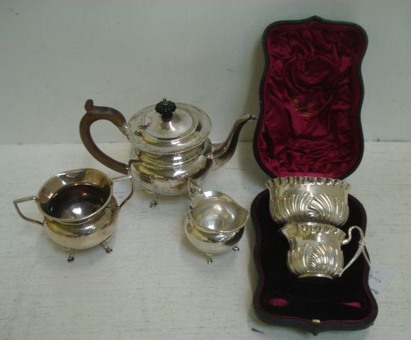 A George V silver three piece bachelor tea service, Birmingham 1925, circular, each on four scroll and hoof feet, a cased late Victorian cream jug and sugar bowl, Birmingham 1891, embossed with curved lobes and flutes, 19ozs and two electroplate toast racks.