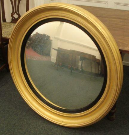 A reproduction Regency style circular convex wall mirror, in moulded giltwood frame with reeded ebonised slip, 100cm.