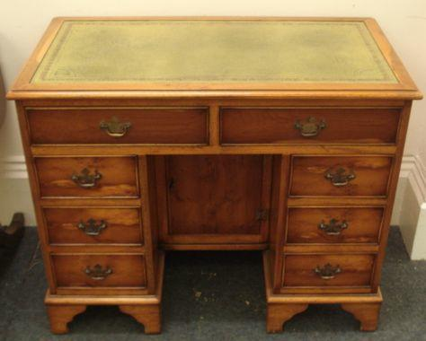 A reproduction George III style yewwood desk, the inset top above eight drawers around a recessed kneehole cupboard, 90cm.