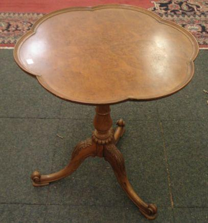 A reproduction George III style walnut tea table, the bird's eye veneered shaped circular tilt-top, on a baluster turned pillar and palmette and scroll carved tripod base, 59cm.