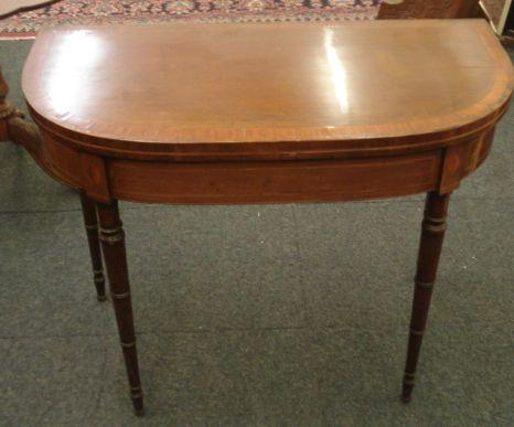 A Regency mahogany card table, satinwood and tulipwood crossbanded, boxwood and ebony strung, the hinged 'D' shape fold over top, on ring turned tapering legs, 92cm.