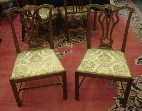 A pair of Chippendale style mahogany dining chairs, with foliate carved pierced ribband vase splat backs, drop-in seats, on moulded square chamfered legs.
