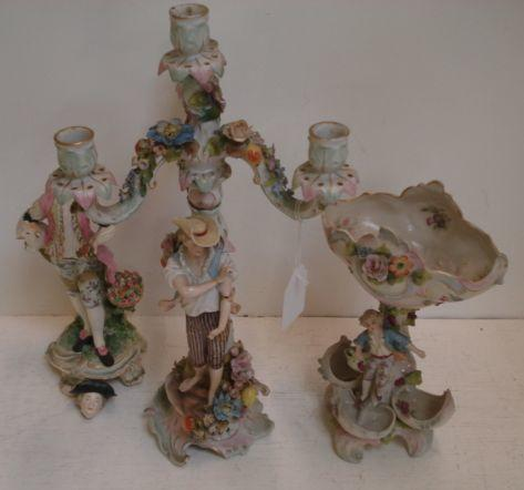 A Sitzendorf porcelain four light candleabrum, encrusted with flowers, with a figure of a young man standing on a scrollwork base, 41.5cm, similar sweetmeat stand and a Derby figure of a shepherd, circa 1760, on a scrollwork base. (3)