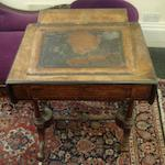 A Victorian figured walnut boxwood and ebony strung desk, with a rising inset central writing slope, having hinged rounded drop leaves, frieze drawer, on dual turned, lobed and fluted end standards, on downswept legs and castors, 69cm. (one leg lacking)