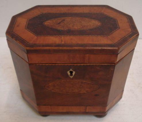 A George III mahogany octagonal tea caddy, satinwood and tulipwood crossbanded, boxwood ebony and chequer strung, the hinged top and front centred by a bird's eye walnut oval,17.5cm, on later bun feet.