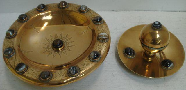 A Victorian circular brass tazza, engraved and set around the edge with twelve agate cabochons another to the centre, 24cm, and a similar inkwell, of hinged divided spherical form on a circular base, set with four banded agate cabochons, 16cm, lacking liner and one ring handle. (2)