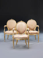 A set of three George III carved giltwood open armchairs attributed to Thomas Chippendale