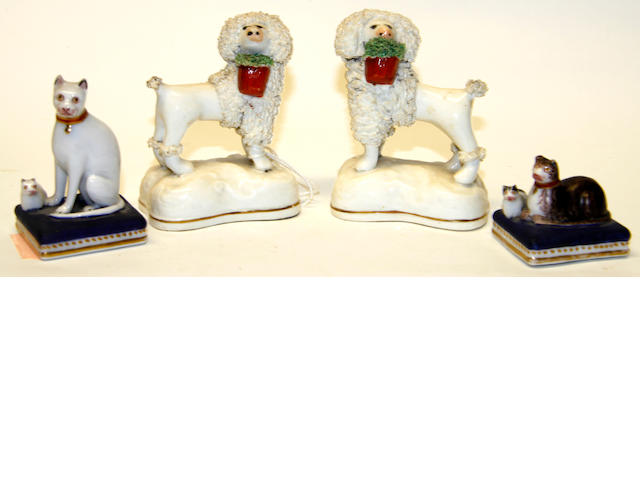 A pair of Staffordshire minature poodles holding baskets;together with a Chamberlains porcelain cat families on cushions (4)