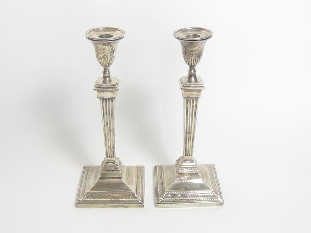 A pair of Corinthian column silver candlesticks by Harrions Bros. & Howson, Sheffield 1923