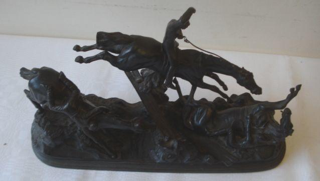 A 19th Century bronzed cast iron figure group, depicting three horseman one taking a jump, one thrown and another fallen, on a naturalistic oval base with central river, 40cm long x 23.5cm max height.