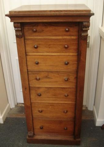 A Victorian rosewood Wellington chest, fitted with seven graduated drawers, side locking pilaster with scroll carved corbels, on a plinth base, 65.5cm.