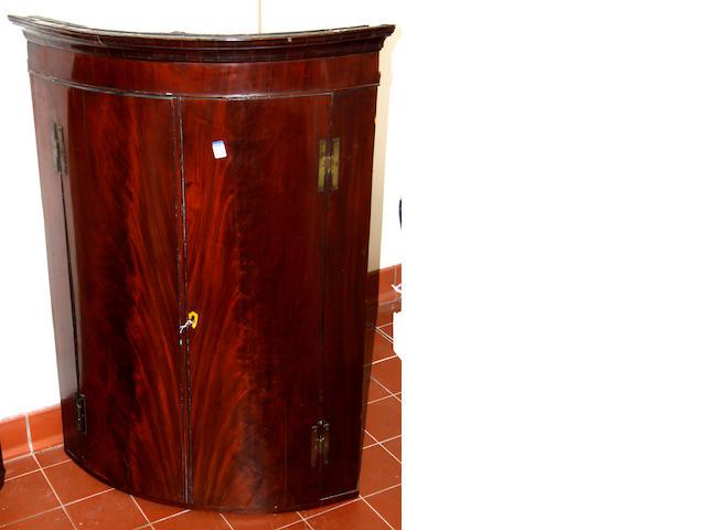 A George III mahogany bowfront hanging corner cabinet,