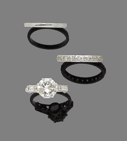 A diamond single-stone ring, a diamond eternity ring and a gold band ring (3)