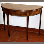 A George III mahogany tea table, the hinged demi line fold over top above a boxwood strung frieze, on moulded square tapered legs and castors, 94cm.