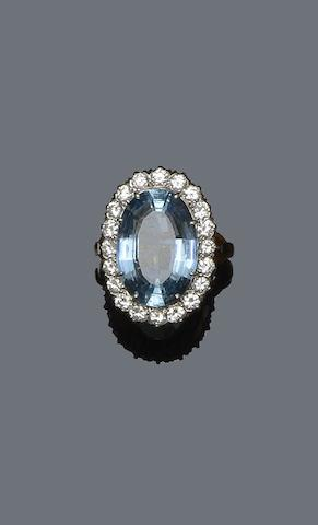 A large oval aquamarine and diamond cluster ring