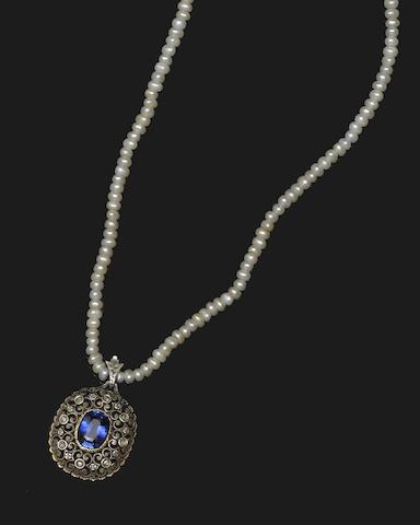 A synthetic sapphire and diamond pendant on a cultured pearl necklace