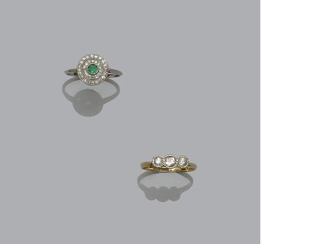 An early 20th century emerald and diamond panel ring and a diamond three stone ring (2)