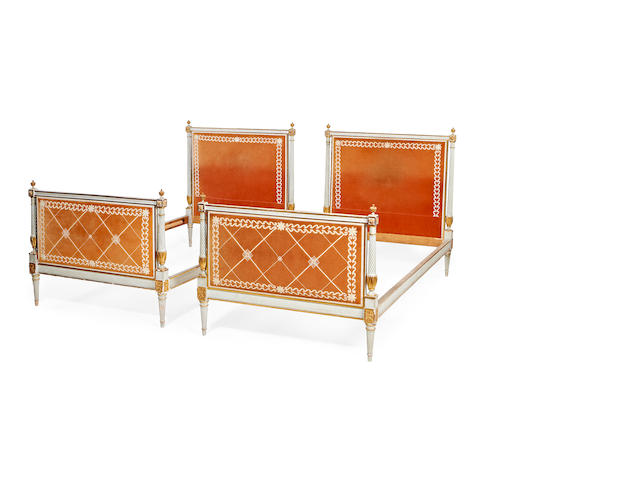 A pair of French early 20th century painted and parcel gilt single bedsin the Louis XVI style