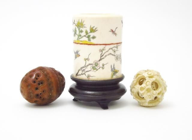 An ivory brush pot and stand, an ivory puzzle ball and a carved coquilla nut Early 20th century