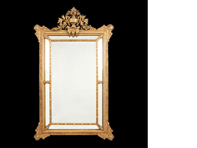 An early 20th century giltwood and composition marginal mirror in the Louis XVI style