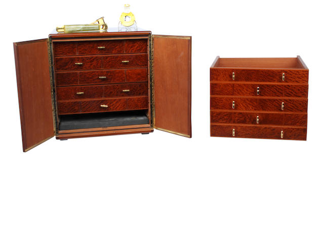 Dunhill: a 20th Century amboyna veneered humidor, two flush doors enclosing five cedar lined drawers and moisture tray, stamped Dunhill made in France', together with five extra trays, also a gilt metal and onyx cigar cutter, and a gilt metal and steel Dunhill circular cigar cutter, 27 x 26 x 28cm.