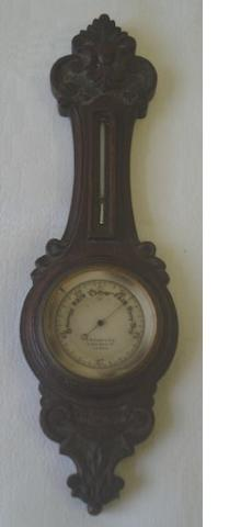 C W Dixey & Son, 8 New bond Street:  a most unusual late Victorian miniature aneroid barometer, the shaped silvered dial with sliding bezel and mercury thermometer in a carved oak scaled down case, 23cm long.