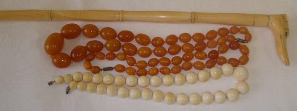 An early 20th Century sectional carved ivory walking cane,the handle carved as a hounds hand, 90cm, a string of graduated ivory beads, circa 1920, 50cm, and two strings of butterscotch amber the oval beads graduated from 10mm to 32mm.