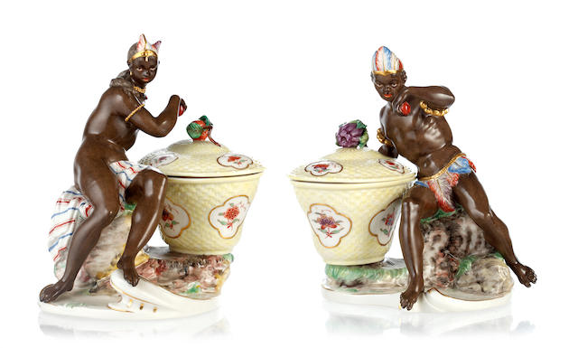 A pair of early 20th Century Nymphenburg figure groups of Africans holding fruit,