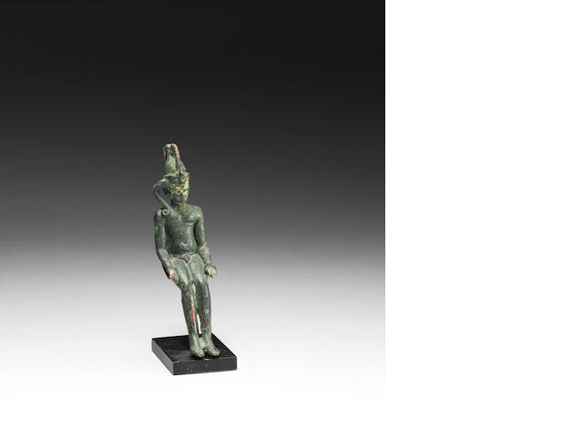 An Egypitian bronze figure of Harpocrates with a stand