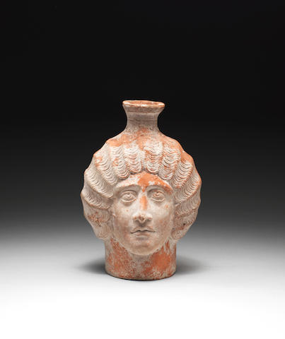 A Roman red slip ware plastic head jug