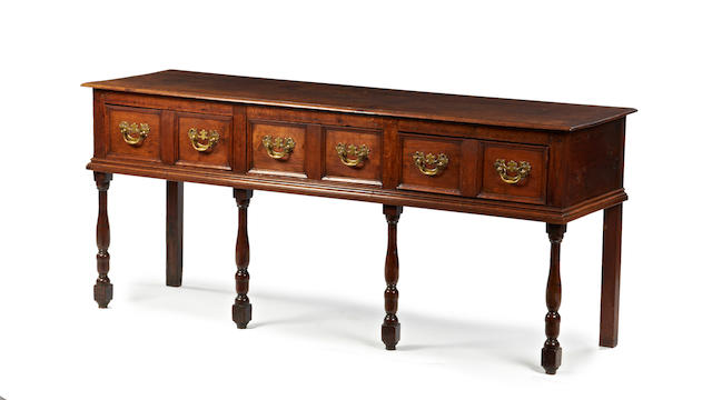 A late 17th Century and later oak dresser, with geometric drawer fronts, raised on turned front supports