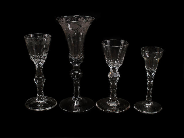 An engraved baluster wine glass and three other glasses with facet-cut stems, 18th century