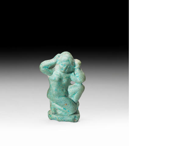 A Ptolemaic pale green glazed composition figure of Aphrodite Anadyomene