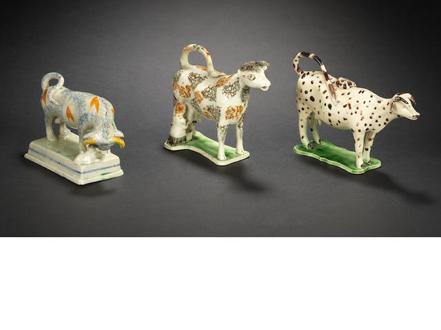 Two creamware cow creamers and covers and a Pratt Ware model of a bull, circa 1800-10
