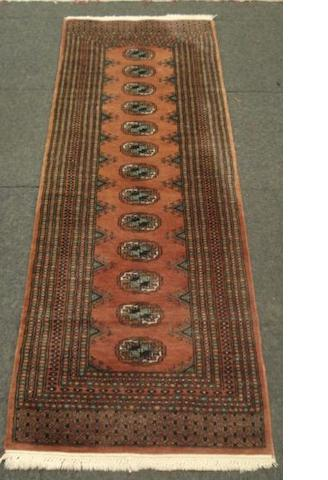 A Pakistan Bokhara runner, with thirteen quartered guls, on a rust round, 1.83 x 62cm, and another runner. (2)