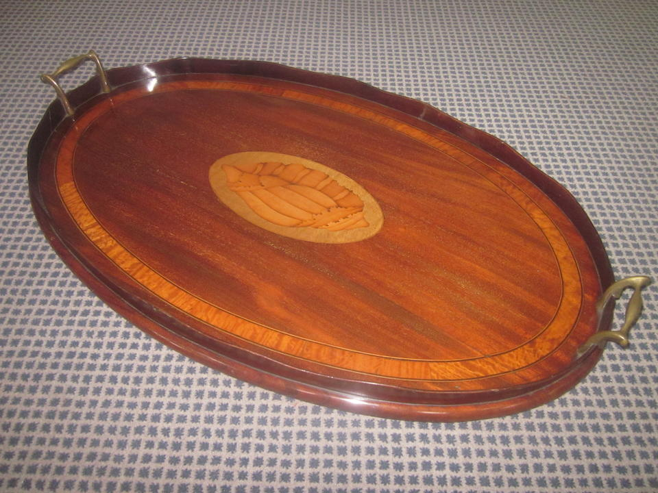 A George III mahogany oval tray, late 18th Century, together with a George III mahogany tray with inlaid shell paterae, early 19th Century (2)